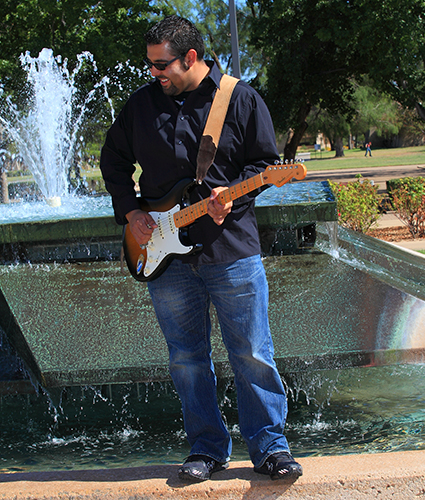 Music student with bass guitar standing by the water fountain on MC campus