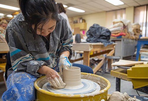 Art student creating a mug in the ceramics class