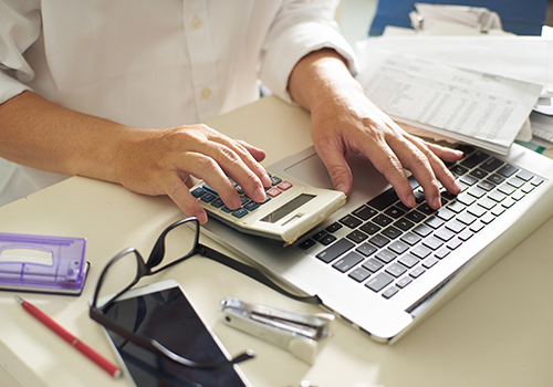 Accountant using a variety of tools at the desk
