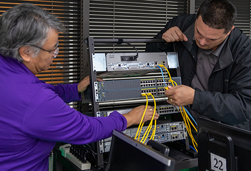 Information Technology student and instructor reviewing the interior of a computer