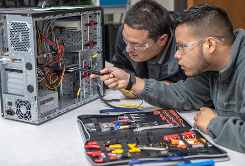 Information Technology students studying the interior of a computer