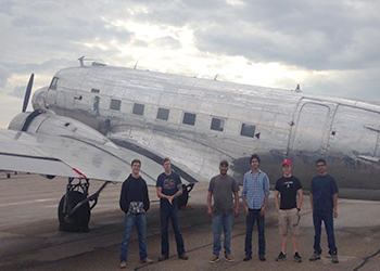 MC students standing in front of a vintage plane