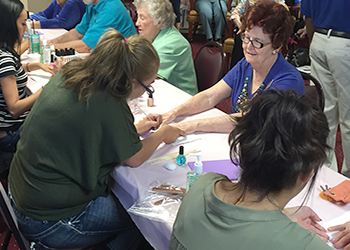 Cosmetology students givinging manicures to senior citizens