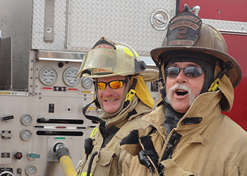 Two Fire Science instructors standing by the fire truck controls