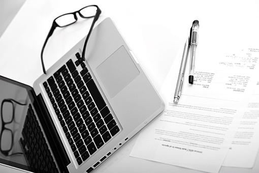 Laptop, papers, pen, and reading glasses on a desk