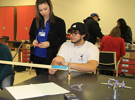 Physics student and instructor in lab experiment