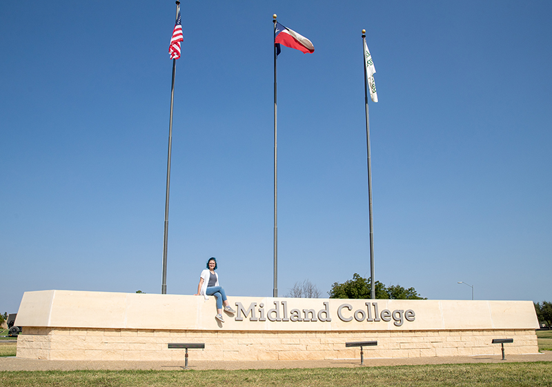 Female student sitting on front entrance sign.
