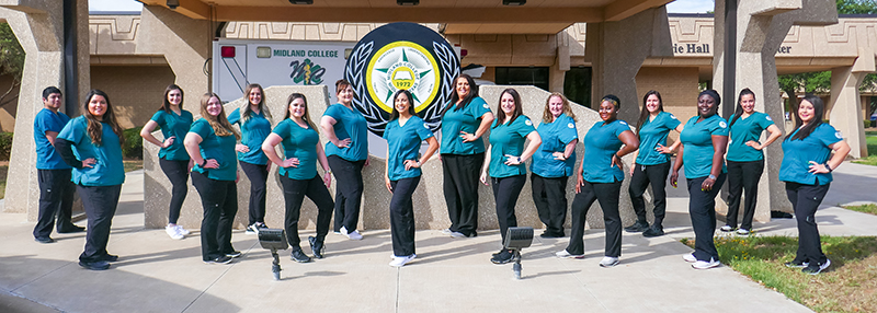 sMay 2021 Associate Degree Nursing graduates standing in front of ambulance bay at F. Marie Hall SimLife center on the main Midland College campus.