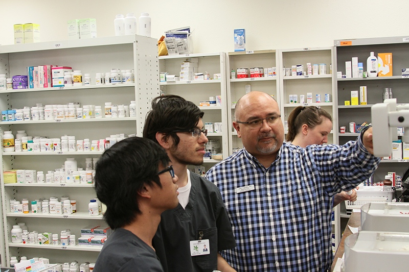 sPharmacist Julio Castillo (far right) explains procedure to Students Khait Sarapao (left) and and Jeremiah Salcido (center) at Graham's Pharmacy on Wall Street in Midland.