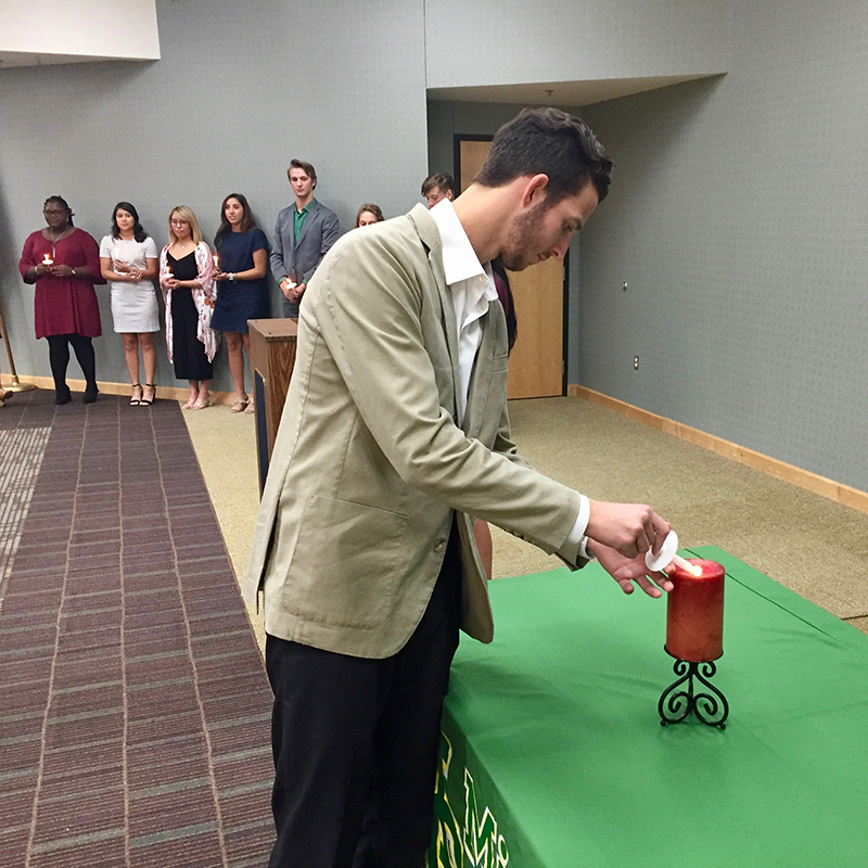 s2019-2020 MC Students in Philanthropy Vice President Lawson Bell lights candle during commissioning ceremony.