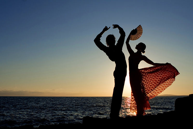 sFlamenco dancers on beach at sunset
